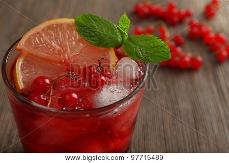 Glass of red currants juice with lemon and ice cubes on wooden table, closeup