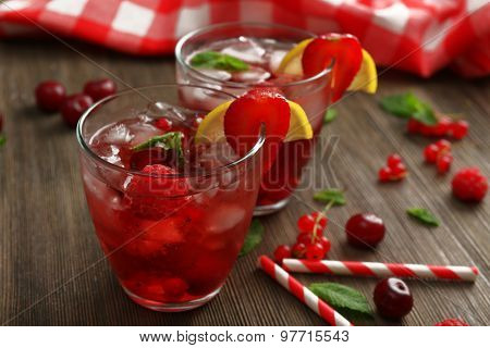 Glasses of berry juice on wooden table, closeup