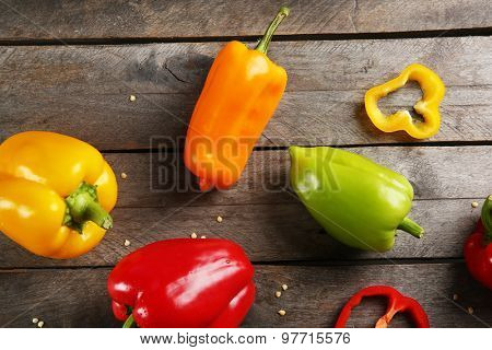 Colorful peppers on rustic wooden table, top view