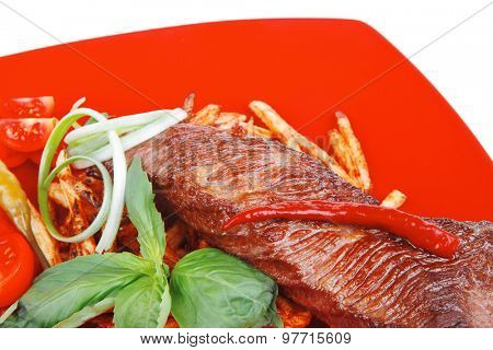 served roasted beef meat steak on potatoes over red dish isolated over white