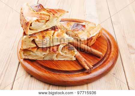 baked food : apple pies on wooden plate over table with cinnamon sticks