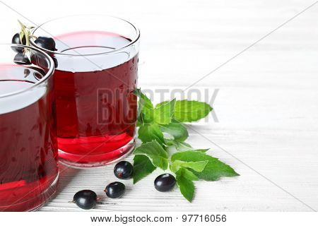 Glasses of fresh blackcurrant juice wooden table background