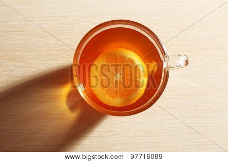 Glass cup of tea with piece of lemon on wooden table, top view