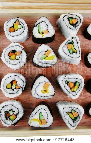 Japanese traditional Cuisine - Roll with Cucumber , Cream Cheese with raw Tuna and Salmon inside. on wooden board . Isolated over white background