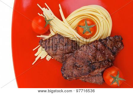 meat grilled beef steak with pasta and tomatoes on red plate isolated over white background