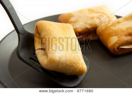 Pancakes With Filling And Scoop on frying pan