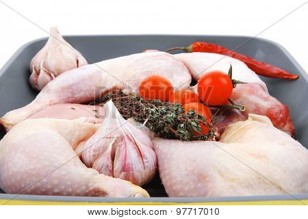 raw chicken legs with tomatoes and thyme on yellow ceramic pan ready to cooking isolated on white background
