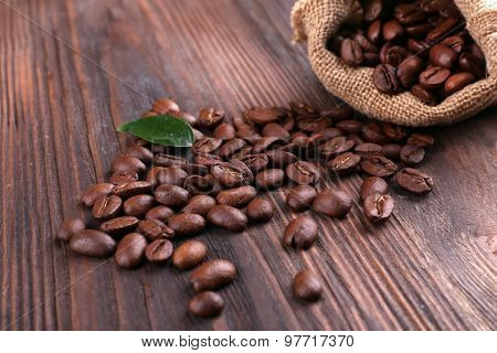 Coffee beans with leaf on wooden table close up