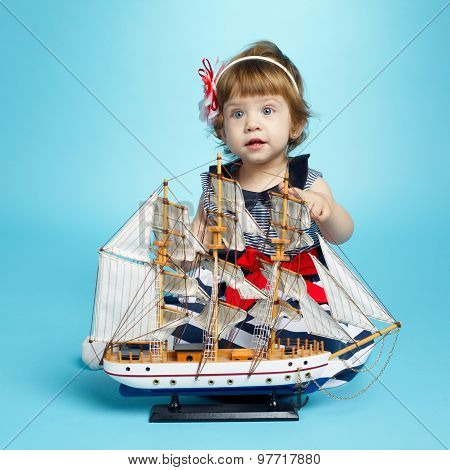 girl in a sea clothes with model ship