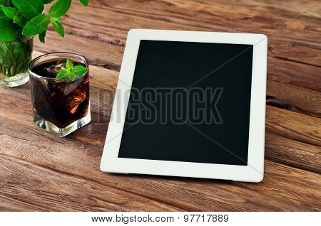 White Tablet Computer With A Glass Glass Of Cola With Ice And Mint