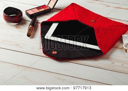 An open red lady's bag with tablet computer in a white wooden table