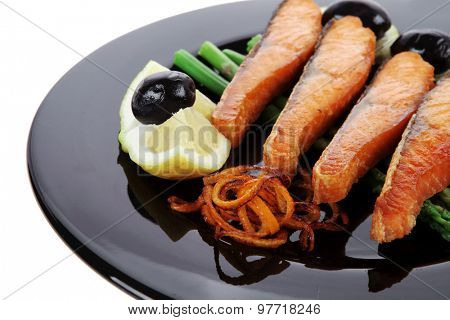 grilled salmon slices with asparagus lemon and olives on black plate isolated over white background