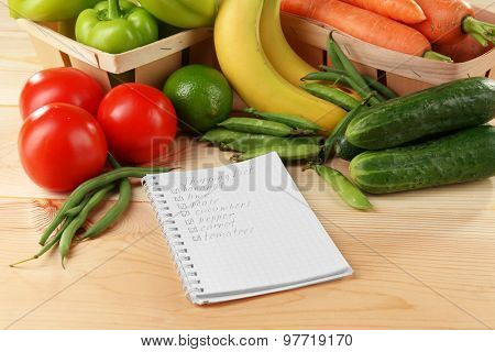 Shopping list wit fresh vegetables and fruits on wooden table, closeup