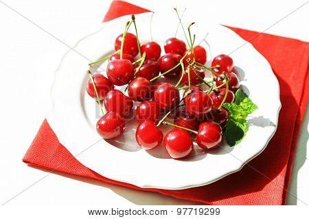 Sweet cherries on plate, on light background
