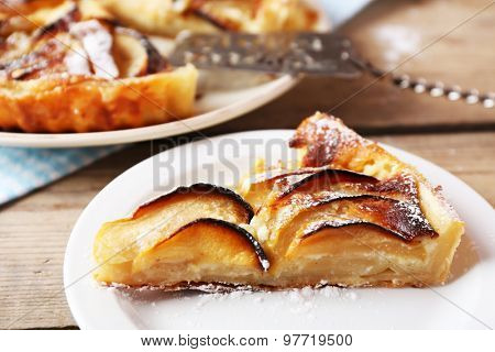 Piece of homemade apple pie on wooden background
