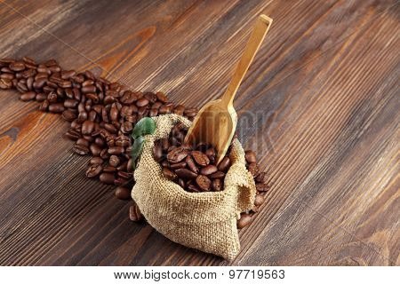 Coffee beans with leaves and spoon in bag on wooden table close up