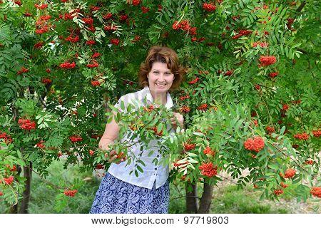 Woman Stands Near Rowan In The Summer