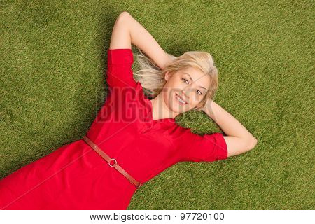 Beautiful blond woman in a red dress lying on grass in a green meadow and looking at the camera