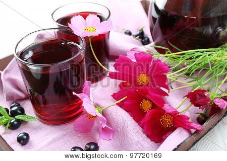 Glasses of fresh blackcurrant juice on wooden tray with pink napkin and flowers, closeup
