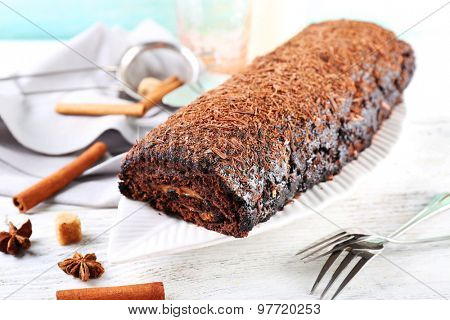 Delicious chocolate roll with spices on wooden table, closeup