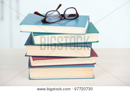 Stack of books with glasses on wooden table in room