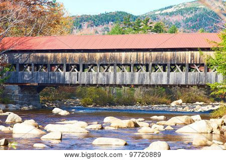 Swift River and old covered bridge at autumn in White Mountain National Forest, New Hampshire, USA.