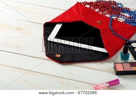 An open red ladies bag with tablet computer in white wooden background