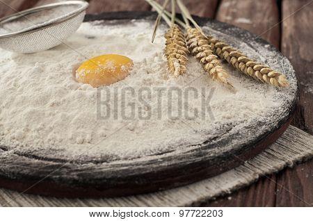 Egg yolk in flour on a wooden table
