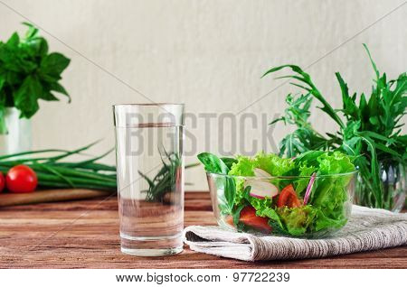 glass of clean water with a salad of fresh vegetables in the rustic kitchen