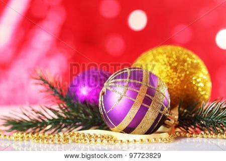 Beautiful Christmas balls on red blurred background