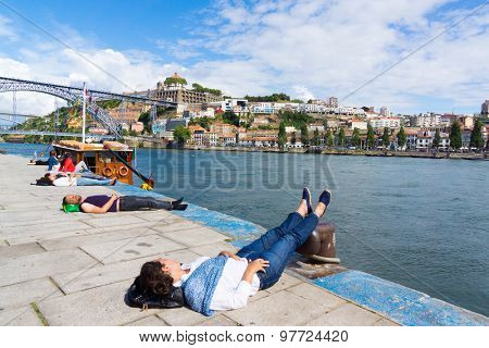 PORTO, PORTUGAL - JUNE, 14: Tourists relax at the embankment near famous landmark Luis bridge at day time on June 14, 2015 in Porto, Portugal