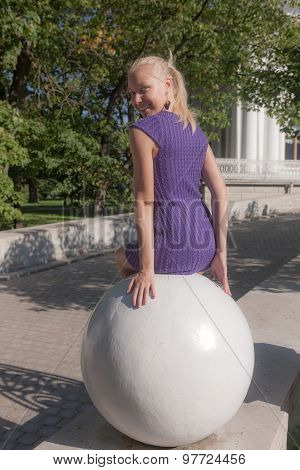 Girl Sitting On A Stone Sphere