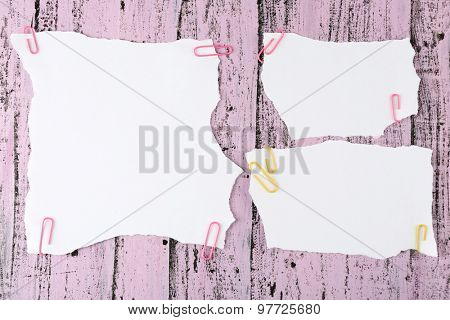 White pieces of paper attached on purple wooden background