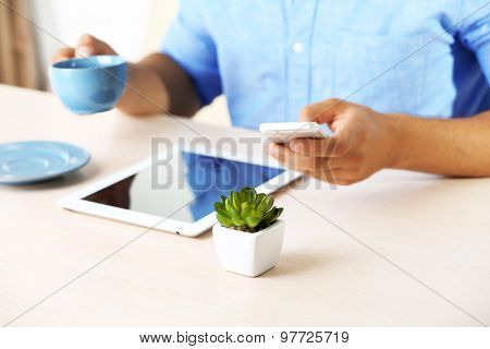 Man with digital tablet on wooden table background