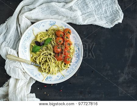Pasta spaghetti with pesto sauce, basil, baked cherry-tomatoes on rustic wooden tabke dark table, to