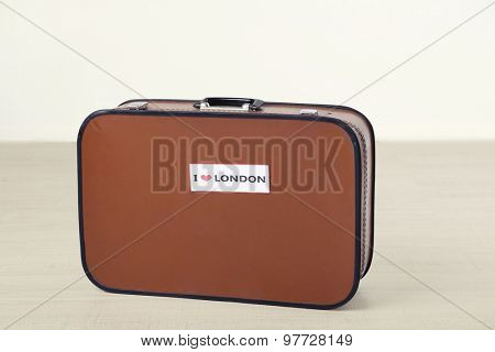 Suitcase with sticker on floor in room