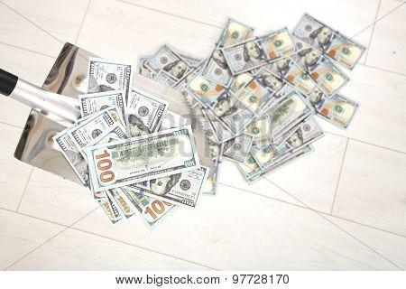 Shovel lifts dollar bills on floor