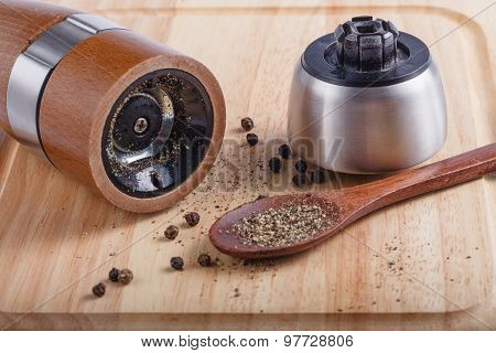 black pepper on the board with a mill