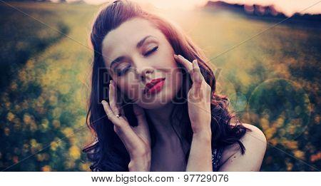 Beautiful woman on summer flower meadow