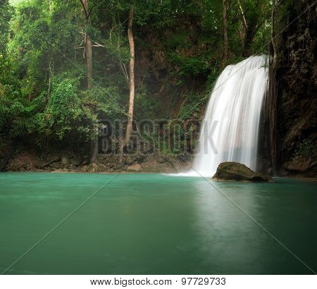Sunlight in jungle rainforest with scenic waterfall flowing in natural pond