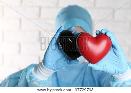 Doctor holding decorative hearts on brick wall background