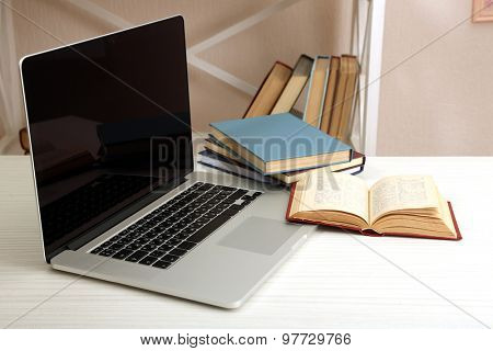 Laptop with books on table in room