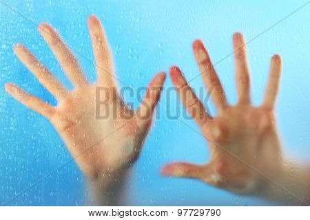 Female hands behind  wet glass, close-up