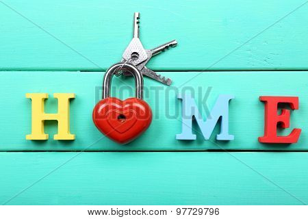 Decorative letters forming word HOME with lock and keys on wooden background