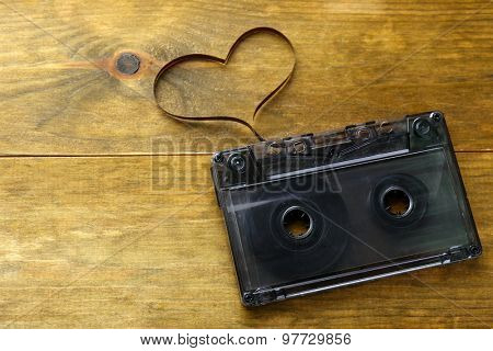 Audio cassette with magnetic tape in shape of heart on wooden background