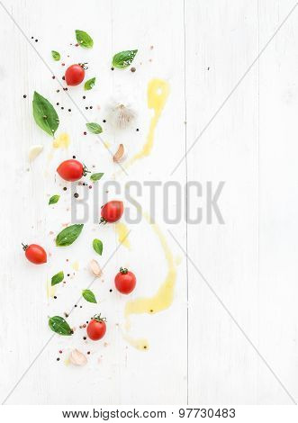 Cherry tomatoes, fresh basil leaves, garlic cloves, spices and olive oil drops on rustic white woode