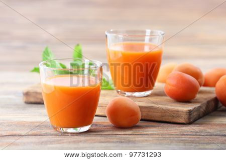 Glasses of apricots juice on wooden background