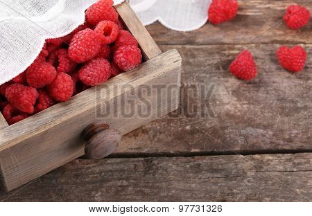 Fresh raspberries in wooden chest on table, closeup