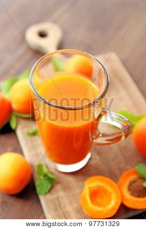 Glass cup of apricot juice and fresh fruits on table close up
