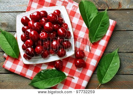 Sweet cherries with green leaves on plate, on wooden background